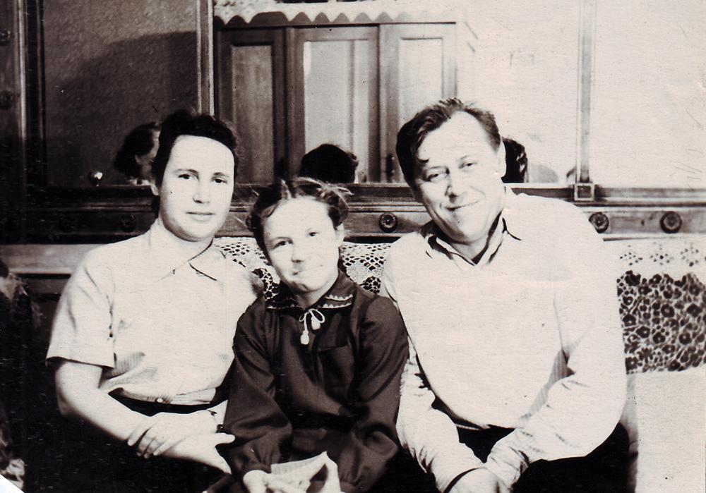 Антонина Еремеевна и Анатолий Емельянович Бочковы с дочкой Нэллой в своей комнате, бывшей зале. На фоне зеркало, сохранявшееся еще с дореволюционных времен. 1953 г.