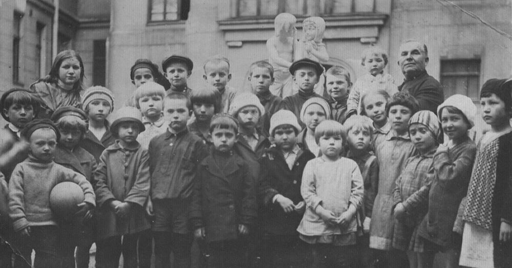 Фотография во дворе дома на фоне корпуса художественных мастерских. Тамара Кузнецова стоит справа от мальчика с мячом в шляпке и в пальто с крупными пуговицами. Предположительно автор фотоснимка отец Тамары Иван Макарович Кузнецов. По воспоминаниям Натальи Саркисьянц, он увлекался фотографией. 13 мая 1931 года