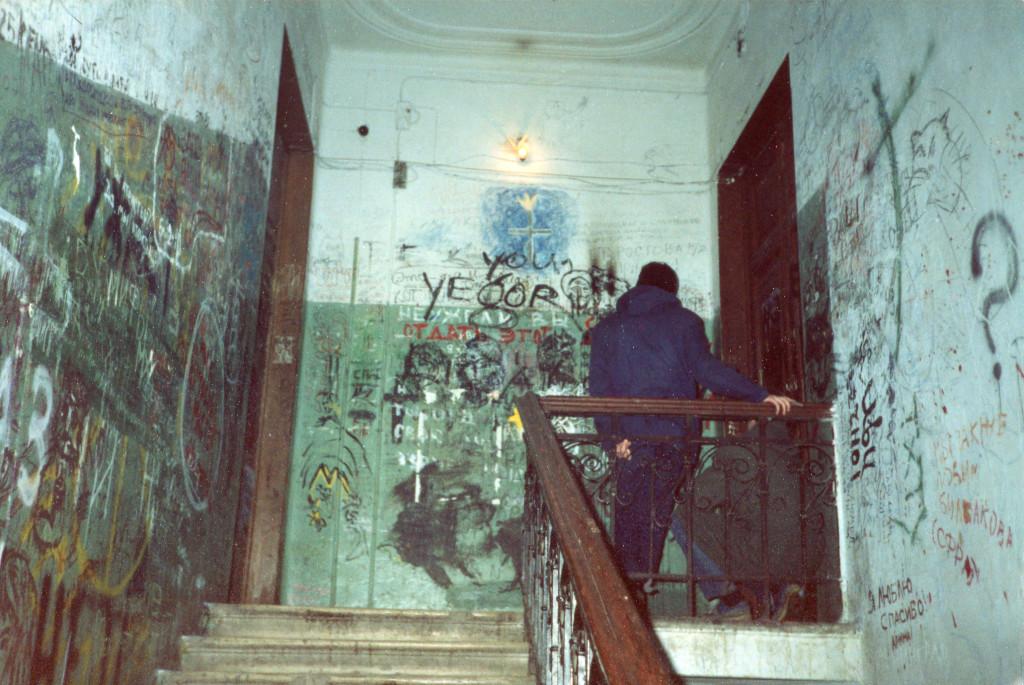 Неизвестный посетитель на верхнем пролете «нехорошей лестницы». Левая дверь на снимке — дверь в «нехорошую квартиру» № 50. Снимок сделан весной 1988 г. Фото: Michael Leetz
