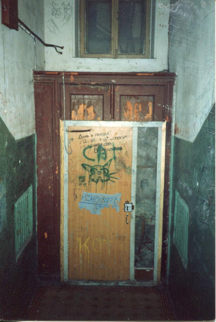 Дверь в 6 подъезд дома 10 на Большой Садовой, которая ведет на «нехорошую лестницу». На двери — граффити с лицом кота Бегемота. Снимок сделан весной 1988 года. Фото: Michael Leetz
