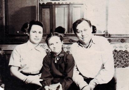 Антонина Еремеевна и Анатолий Емельянович Бочковы с дочкой Нэллой в своей комнате, бывшей зале. На фоне зеркало, сохранявшееся еще с дореволюционных времен. 1953 год